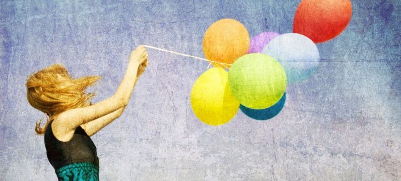 woman holding balloons in the wind